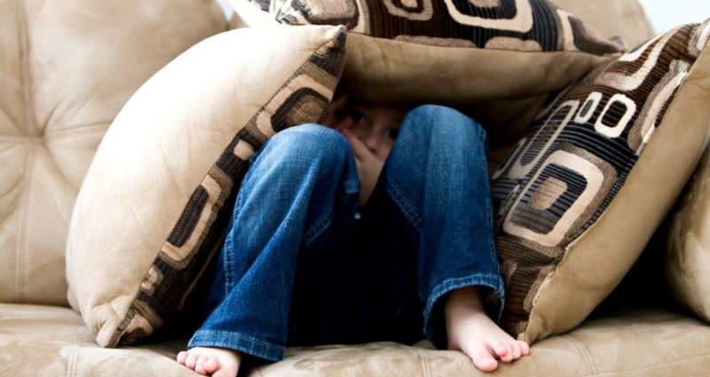Person hiding under sofa cushions