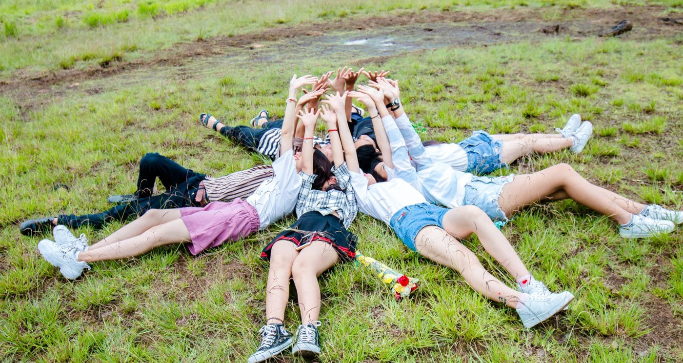 Group of people lying on the floor with their arms in the air